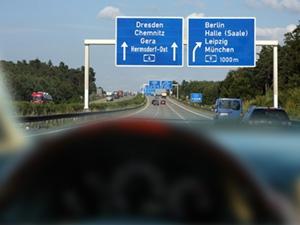 Blick durch die Frontscheibe eines Autos. Die Autobahnbeschilderung in der Ferne ist scharf zu erkennen, der Blick auf den Tacho allerdings ist unscharf.