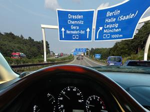 Blick durch die Frontscheibe eines Autos, in der Ferne ist eine Autobahnbeschilderung zu sehen. Die Ansicht ist verkrümmt und in sich verzogen.